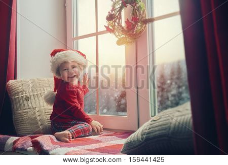 Merry Christmas and happy holidays! Cute little baby girl sitting by the window and looking at the winter forest. Room decorated on Christmas. Kid enjoys the snowfall.
