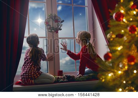Merry Christmas and happy holidays! Cute little children girls sitting by window and looking at christmas star. Room decorated on Christmas. Kids enjoy the holiday.