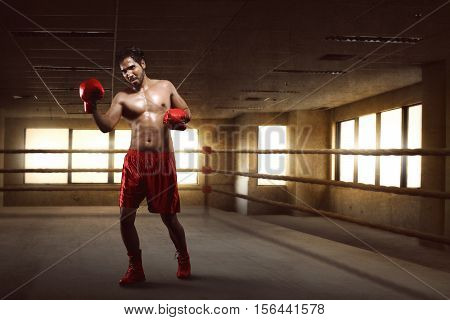 Portrait Of Asian Boxer Performing Uppercut On The Boxing Ring