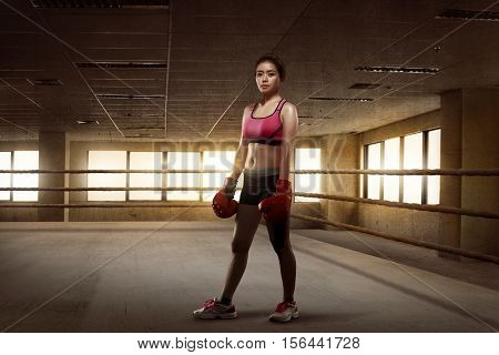 Beauty Asian Girl Boxer With Red Gloves Standing In The Boxing Ring