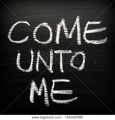 The phrase Come Unto Me written by hand in white chalk on a blackboard. Words from a passage in Matthew in versions of the Bible