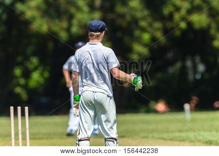 Cricket game teenagers schools game wicket keeper batsman bowler action photo.