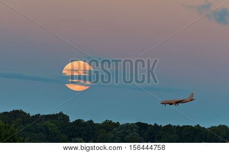 Super moon and landing airplane above forest, Europe