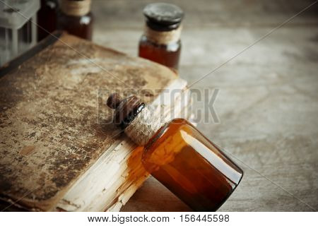 Vintage glass bottle with old book on wooden background, closeup
