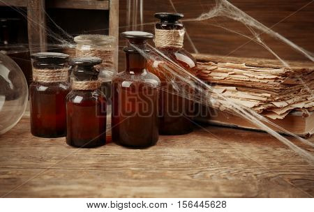 Vintage glass bottles and old books with spiderweb on wooden table, closeup