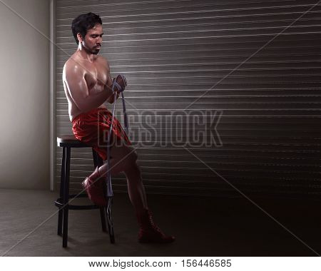 Asian Man Boxer Sitting While Wearing White Strap