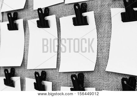Notice board with clips holding blank square paper notes close up. Viewed at an angle in black and white