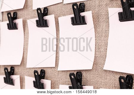 Notice board with clips holding blank square paper notes close up. Viewed at an angle