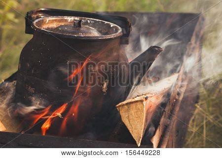 Old Used Black Boiling Teapot On Fire