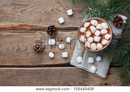 Cup of hot chocolate on wooden rustic table from above. Delicious winter drink. Flat lay.