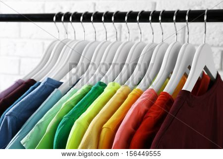 Colorful t-shirts on hangers against light background, close up view