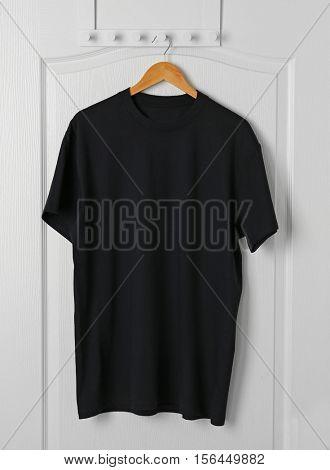 Blank black t-shirt hanging on white door