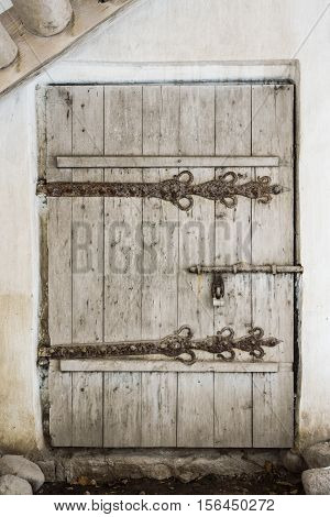 old wooden door with wrought iron elements isolated on white background