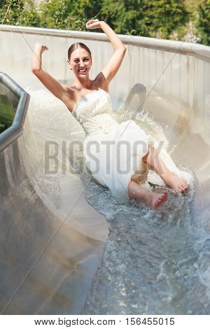 Young bride in a wedding dress having fun in gown in a water chute