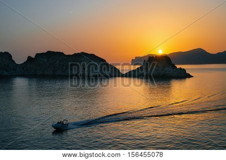 The boat yacht sails near Santa Ponsa coastline at sunset in Morro d'en Pere Joan bay in Mallorca Balearic islands of Spain. Es Malgrat rocks.