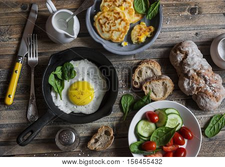 Snack or breakfast table - fried egg corn fritters vegetables homemade bread on wooden background top view