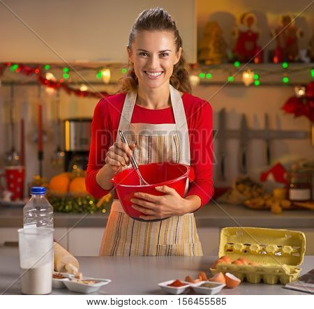 Happy Young Housewife Whisking Dough In Christmas Decorated Kitchen