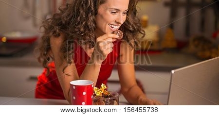 Happy Young Housewife With Christmas Snacks Using Laptop In Kitc