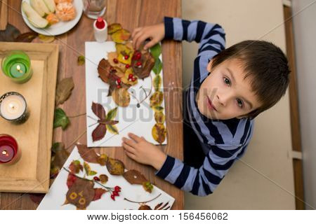 Sweet Child, Boy, Applying Leaves Using Glue While Doing Arts And Crafts In School