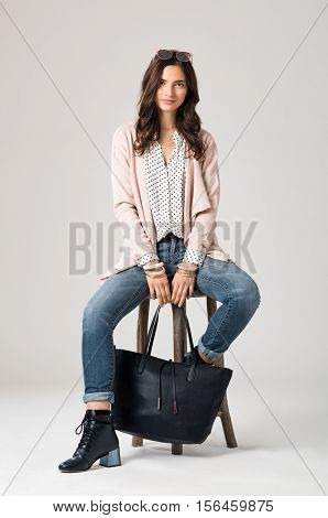 Portrait of young brunette woman sitting on wooden stool and looking at camera. Smiling fashion girl wearing stylish clothes. Happy beautiful woman with sunglasses and shopping bag sitting on stool.