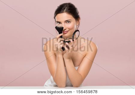 Young beautiful woman holding foundation box and brush smiling. Smiling woman holding blusher box isolated on pink background. Beauty brunette girl having fun and joking with make up and face powder.