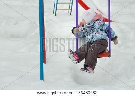 Little girl is riding on frosty winter playgrounds swing is covering with white snow outdoors