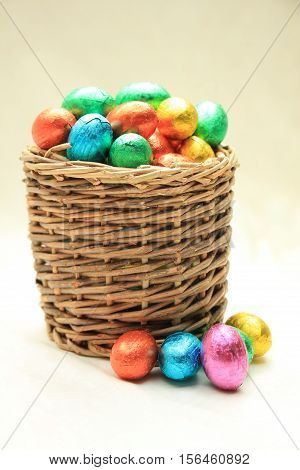 foil wrapped chocolate easter eggs in a wicker basket