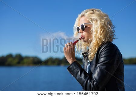 Woman smoking electronic cigarette while sitting outdoors