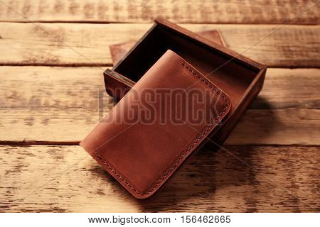Stylish leather passport cover with box on wooden background