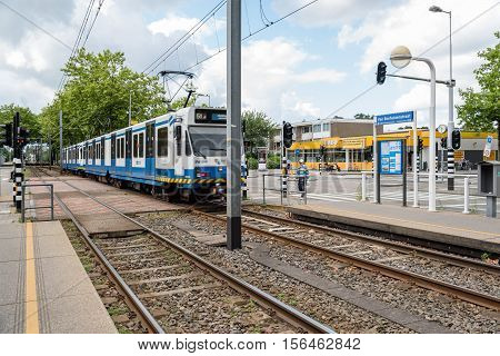 Amsterdam Netherlands - August 1 2016: Tram crossing the street. The Amsterdam Tram is one the largest tram network in Europe.