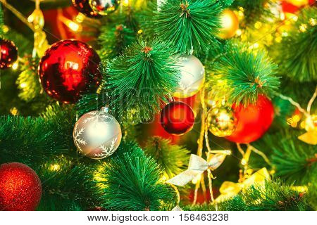 Beautiful decorated Christmas tree with red and goldish baubles and garland in the new-year background. The idea for postcards. Soft focus. Shallow DOF