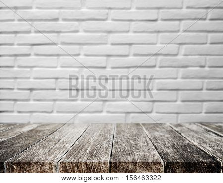 Wood plank tabletop, with defocus brick white wall texture background