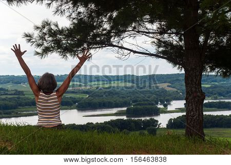 The female figure with raised up arms on the background of the Mississippi River, Illinois, USA