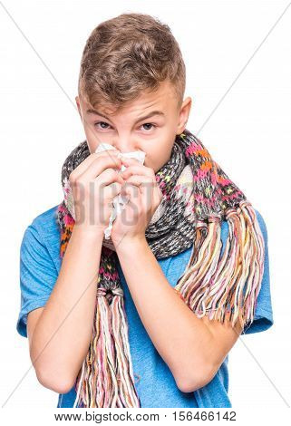 Healthcare and medicine concept - ill teen boy with flu blowing nose. Teenager wipes a nose a napkin. Child wearing blue t-shirt and scarf, isolated on white background.