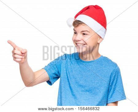 Half-length portrait of caucasian teen boy wearing Santa Claus hat. Teenager in blue t-shirt pointing to somewhere. Holiday Christmas concept - happy cute child isolated on white background.