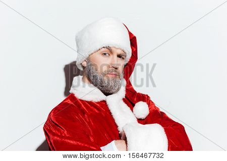 Confident bearded man in santa claus costume standing with arms crossed