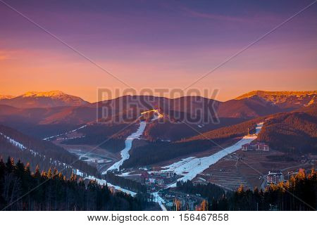 Ski resort in colourful sunset light. View from the top: ski tracks, pine tree forest and mountains in the background. Winter holidays in Bukovel, Carpathians, Ukraine, Europe