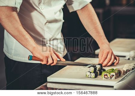 Chef in hotel or restaurant kitchen cooking, only hands. He is working on maki rolls. Preparing sushi set