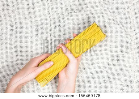 Raw spaghetti in female hands flat lay. Top view of bunch uncooked spaghetti on light canvas background