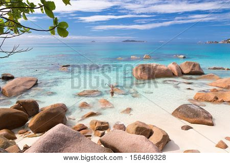 Happy woman arms rised wearing stylish bikini enjoying swimming and snorkeling at amazing Anse Lazio beach on Praslin Island, Seychelles. Summer vacations on picture perfect tropical beach concept.