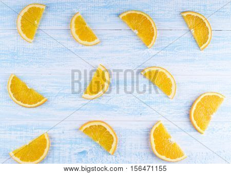 halves of an orange background. Orange on blue wooden background top view. Overhead shot of oranges on an old wooden table
