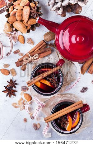 Hot mulled wine in a red mug for winter and fall holidays. Christmas drink in rustic style. Selective focus, top view, overhead flat lay