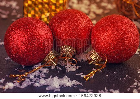 red glittery Christmas balls on black background