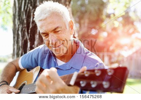 Senior man plying guitar outdoors