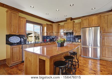 Wooden Kitchen Interior With An Island And Steel Appliances.