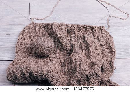 Knitted Fabric With Spokes Lying On A Wooden Table