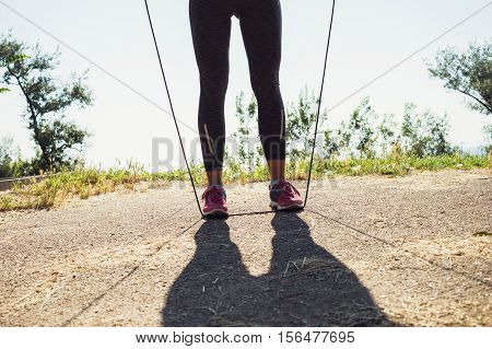Female feet in running shoes and a skipping rope in the summer outdoors closeup