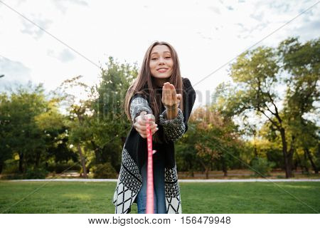 Cheerful cute young woman walking and playing with dog on lead outdoors