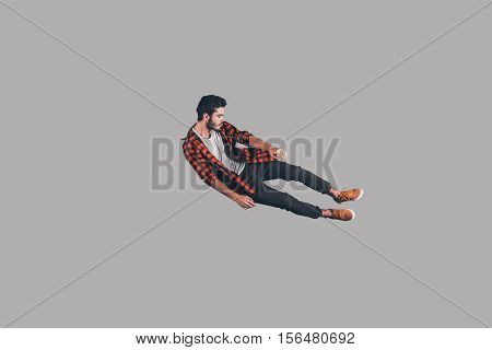 In mid-air. Mid-air shot of handsome young man jumping and gesturing against background