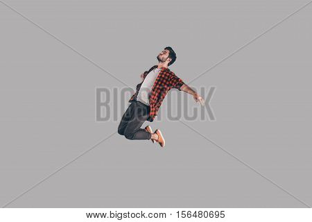 Free falling. Mid-air shot of handsome young man jumping and gesturing against background